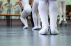 Piernas del primer del pequeño grupo de las bailarinas en los zapatos blancos que practican en estudio del ballet clásico fotos de archivo