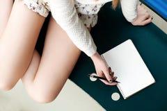 Piernas del ` s de la muchacha, escribiendo en cuaderno Imagen de archivo libre de regalías