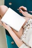 Piernas del ` s de la muchacha, escribiendo en cuaderno Fotos de archivo libres de regalías