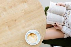 Piernas del ` s de la muchacha, libro, taza de café en la tabla Fotos de archivo