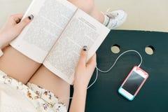 Piernas del ` s de la muchacha, sosteniendo el libro, teléfono móvil próximo Imagen de archivo libre de regalías