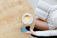 Piernas del ` s de la muchacha, taza de café, libro y teléfono móvil Fotos de archivo libres de regalías