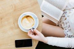 Piernas del ` s de la muchacha, taza de café, libro y teléfono móvil Fotos de archivo