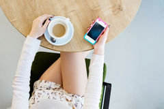 Piernas del ` s de la muchacha, taza de café y teléfono móvil Imagen de archivo