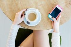 Piernas del ` s de la muchacha, taza de café y teléfono móvil Fotografía de archivo