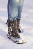 Piernas del ` s de la mujer con los tejanos y los zapatos negros en una nieve Imágenes de archivo libres de regalías