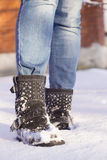 Piernas del ` s de la mujer con los tejanos y los zapatos negros en una nieve Fotos de archivo