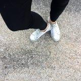 Piernas del ` s de la mujer de la moda de los jóvenes con las zapatillas de deporte, zapatos blancos en fondo del piso Fotografía de archivo