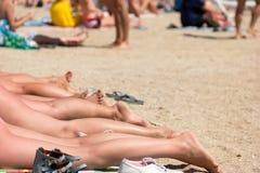 Piernas del ` s de las mujeres en la playa Imagen de archivo libre de regalías