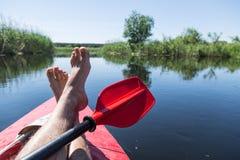 Piernas del ` s del hombre sobre la canoa fotografía de archivo