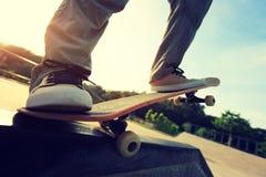 Piernas del skater que montan el monopatín en el skatepark de la ciudad Foto de archivo libre de regalías