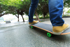 Piernas del skater que montan el monopatín en el skatepark de la ciudad Fotos de archivo libres de regalías