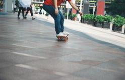 Piernas del skater que montan el monopatín en la calle de la ciudad foto de archivo libre de regalías