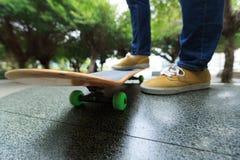 Piernas del skater que montan el monopatín en el skatepark de la ciudad Imagen de archivo