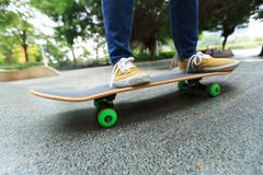 Piernas del skater que montan el monopatín en el skatepark de la ciudad Imagen de archivo libre de regalías