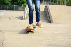 Piernas del skater que montan el monopatín en el skatepark de la ciudad Fotografía de archivo libre de regalías