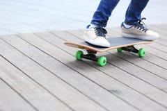 Piernas del skater que montan en el monopatín en ciudad Foto de archivo libre de regalías