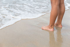 Piernas del soporte de los niños en la playa Fotos de archivo libres de regalías