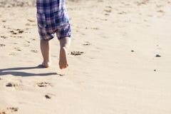 Piernas del soporte de los niños en la playa Pies del bebé en la arena Fondo de la playa del verano Concepto de los días de fiest foto de archivo