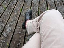 Piernas del varón adulto vistas cruzadas mientras que se sienta en un banco de parque fotografía de archivo libre de regalías