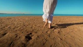 Piernas del vestido largo blanco que lleva de la muchacha cauc?sica que camina la arena descalza en la playa del mar almacen de video
