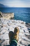 Piernas del viajero en botas amarillas cerca del mar Imágenes de archivo libres de regalías