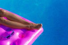 Piernas delgadas jovenes del ` s de la mujer en un colchón de aire en piscina imagen de archivo libre de regalías