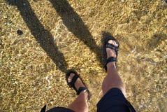 Piernas desnudas con los pies de la sandalia que se colocan en playa de la marea baja foto de archivo libre de regalías
