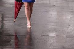 Piernas desnudas de la mujer con los talones y el paraguas Fotos de archivo libres de regalías