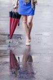 Piernas desnudas de la mujer con los talones y el paraguas Imágenes de archivo libres de regalías