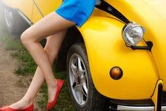 Piernas desnudas y atractivas de una muchacha que se sienta en un coche amarillo retro en verano Foto de archivo