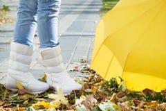Piernas en botas con el paraguas Foto de archivo libre de regalías