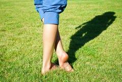 Piernas en hierba con la sombra Fotos de archivo
