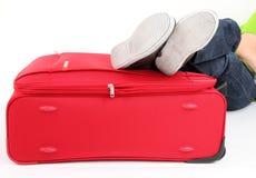 Piernas en la maleta roja Fotos de archivo
