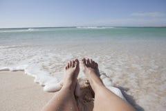 Piernas en la playa Foto de archivo libre de regalías