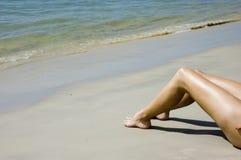 Piernas en la playa Foto de archivo
