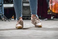 Piernas en pantalones cortos del dril de algodón y zapatos de los deportes fotografía de archivo libre de regalías