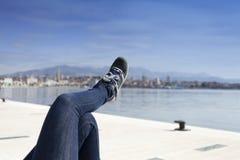 Piernas en pantalones de los vaqueros y zapatos azules del deporte en costa de mar Imagen de archivo libre de regalías
