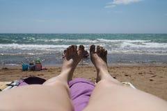 Piernas en un ocioso del sol en la playa el día de fiesta imagen de archivo libre de regalías