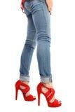 Piernas en vaqueros y zapatos rojos con los tacones altos imagenes de archivo