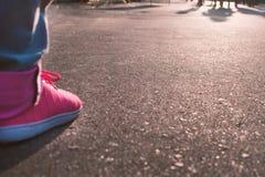 piernas en zapatillas de deporte brillantes en el asfalto imágenes de archivo libres de regalías