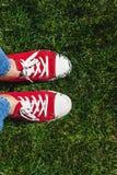Piernas en zapatillas de deporte rojas viejas en hierba verde Visión desde arriba El co Imagenes de archivo