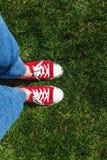 Piernas en zapatillas de deporte rojas viejas en hierba verde Visión desde arriba El co Foto de archivo libre de regalías