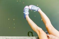 Piernas en zapatillas de deporte sobre el agua Imágenes de archivo libres de regalías