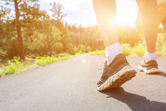 Piernas en zapatos del deporte en el camino en el primer de la puesta del sol Fotos de archivo