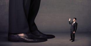 Piernas enormes con el pequeño hombre de negocios que se coloca en concepto delantero Imagen de archivo
