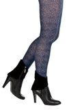 Piernas femeninas bien proporcionadas en panty y botas Foto de archivo libre de regalías