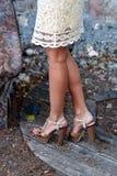 Piernas femeninas bronceadas en talones Imagen de archivo