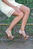 Piernas femeninas bronceadas en talones Fotos de archivo