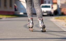Piernas femeninas con los pcteres de ruedas en línea Carretera de asfalto en la ciudad con los coches y los edificios imagen de archivo